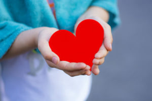 Little girl holding red heart in her hands.