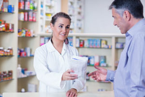 Trainee giving a bag of pills to a customer in a drugstore
